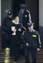 A nun is escorted out of the convent in the town of Kazimierz Dolny south east of Warsaw