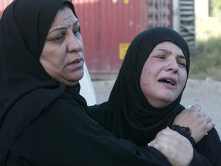 A woman cries while waiting to claim the body of a relative, killed during a U.S. strike, outside a hospital morgue in Baghdad