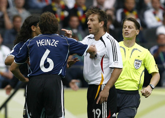 Argentina's Sorin and Heinze confront Germany's Schneider as referee Michel of Slovakia intervenes in Berlin
