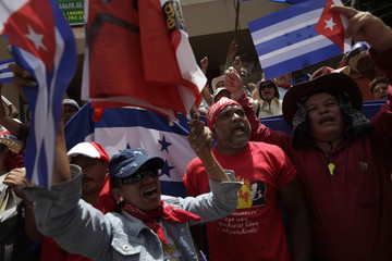"Supporters of Honduras' ousted president Zelaya wave during a protest for the liberation of the ""Cuban Five"", outside the U.S. Embassy in Tegucigalpa"