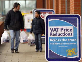 Shoppers leave a Tesco supermarket advertising VAT reductions in Birmingham, central England