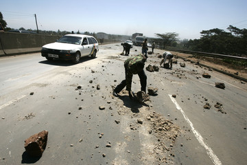 Police officers clear a roadblock to restore traffic on the country's main highway in Kikuyu village