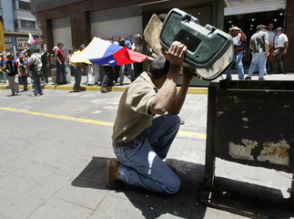 VENEZUELAN MAN COVERS HIMSELF FROM FIRE DURING A MARCH IN CARACAS.