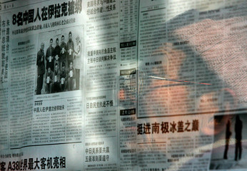 A Chinese resident is reflected in a window as he reads a newspaper displayed in Shanghai.