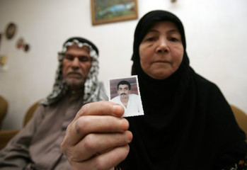Iraqi woman holds a picture of her son Abed Abbas as her husband looks on in their home in Baghdad