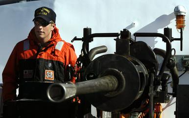 COAST GAURD OFFICER STANDS NEXT TO MACHINE GUN IN BOSTON HARBOR.