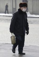 A man wears a face-mask as he walks in North Korean capital of Pyongyang