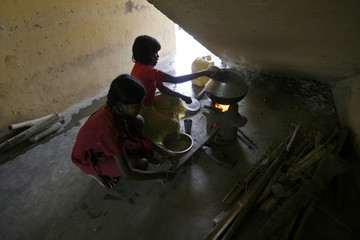 Flood-affected girls prepare food at a flood relief camp at Valuka village