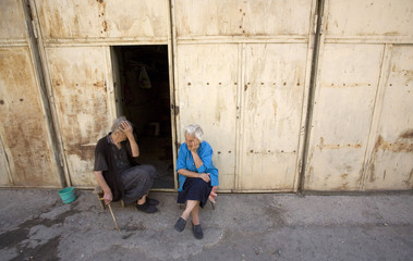 Helen, 85, and Tina, 75, sit outside a garage two weeks after an air strike destroyed their home in Gori