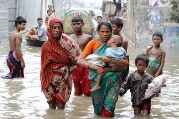 BANGLADESHIS WADE THROUGH FLOODED STREET IN DHAKA.