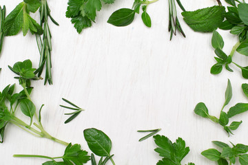 Green fresh herbs mix on white wooden background , top view