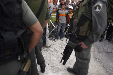 Palestinians stand behind barbed wire during a protest near Bethlehem