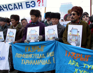 MONGOLIAN FARMERS AND DRIVERS HOLD PICTURES OF TRACTORS DURING A PROESTIN ULAN BATOR.