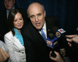 Republican presidential candidate and former New York City Mayor Rudy Giuliani speaks with local television reporters as he departs a campaign rally in West Palm Beach