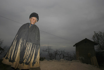 Leize Wuliang, a 78-year-old leper from the Yi ethnic minority, stands outside his house in Dayingpan Village