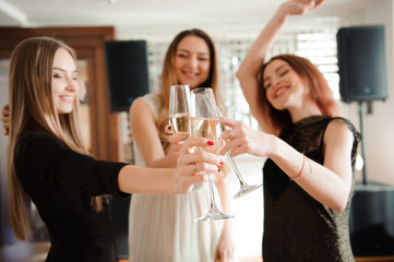 Group people with champagne dancing at the party.
