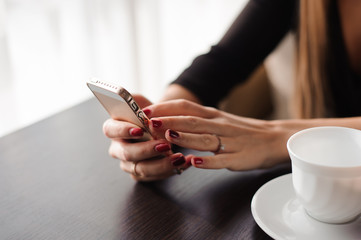 Close up of hands woman using her cell phone in restaurant, cafe