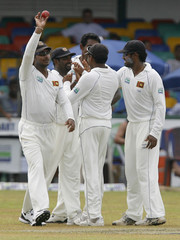 Sri Lanka's Prasanna Jayawardene holds up the ball that was caught by team mate Muttiah Muralitharan to dismiss New Zealand's Martin Guptill, as team mate celebrate in the background, during  the second day of their second test cricket match