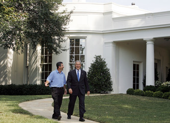 U.S. President George W. Bush walks from the Oval Office with Hurricane Katrina survivor Rockey Vaccarella at the White House