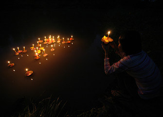 A villager prays before floating a kratong into a pond during the Loy Kratong festival in Nakhonsawan province, north of Bangkok