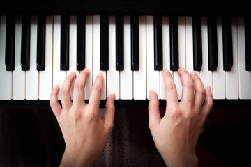 Woman hands playing piano. Music and art background. Top view.