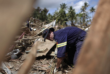 Emergency worker from Australia moves debris as he searches for tsunami victims on Samoa's southern coast
