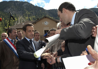 France's President Nicolas Sarkozy shakes hand with supporters as he arrives at the Petit-Bornand