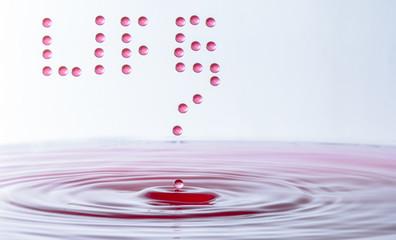 Leben mit Wassertropfen - Life geschrieben mit fallenden Wassertropfen in das rote Wasser