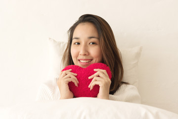 women wake up and holding Heart pillow in the moring