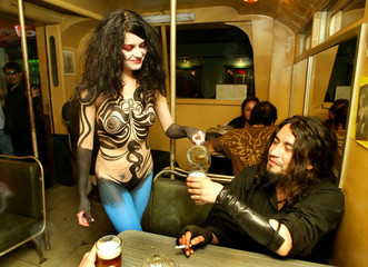A naked woman with her body painted attends clients in a bar in Valparaiso.
