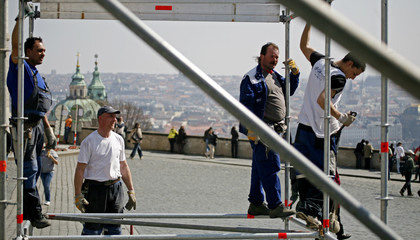 Workers stand on a scaffolding as they fix platform at Hradcanske Square in central Prague