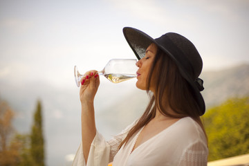Beautiful young lady drinking wine on balcony with excellent view