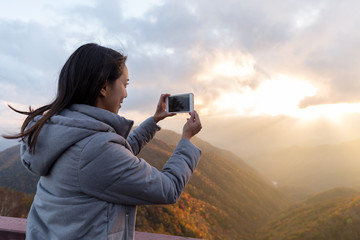 Young Woman taking photo on cellphone at Mount Hangetsuyama during sunset