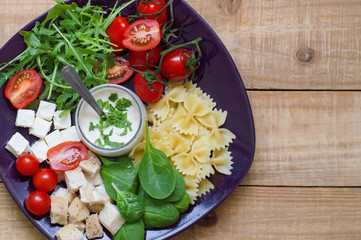 Background with fresh homemade pasta salad. Farfalle, spinach leaves, chopped chicken breast, cherry tomatoes, feta cubes, rocket leaves and white sauce served on wooden table