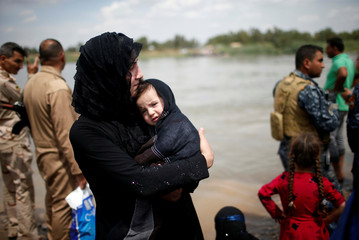 Displaced Iraqis wait to cross the Tigris River by boat after the bridge has been temporarily closed in western Mosul