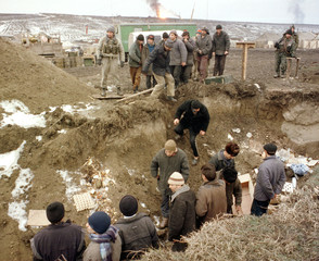 ARRESTED CHECHEN MEN DESCEND INTO A TRENCH.