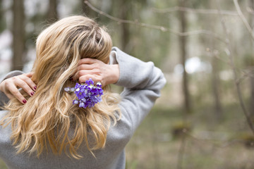 Back view on young blond woman with a bunch of blue srping snowdrops in her hand. Girl with flowers on nature background