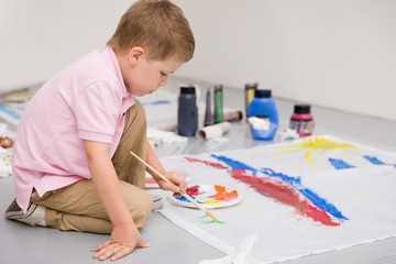 Cute kid boy sitting on the floor and drawing with colorful paints. Child making flag craft. Education, creativity, school activities.
