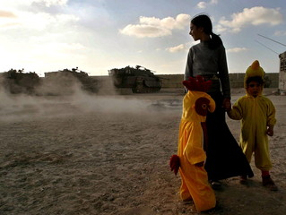 Young Jewish settlers dressed for the Jewish Purim holiday stand near Israeli army armoured vehicles..