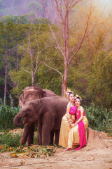 Beautiful Asian Woman wears thai dress with her elephant