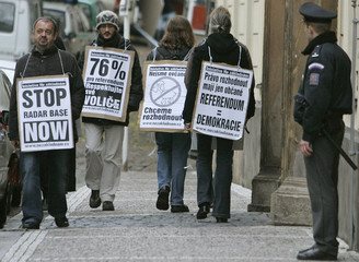 Demonstrators are seen with placards as they walk past the Czech Parliament in Prague