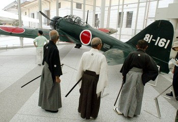 """Japanese martial art masters look at a Zero fighter (or """"Zerosen"""" in Japanese), a carrier-borne airc.."""