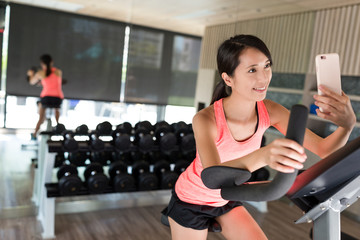 Woman cycling and taking selfie in the gym room