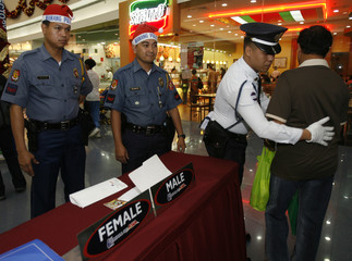 Policemen wearing Santa Claus hats stand guard as a security guard inspects a shopper inside a crowded mall in Manila