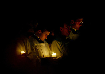 PRIESTS HOLD CANDLES DURING A MASS IN ST. PETER'S BASILICA.