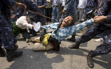 Riot policemen detain Tibetan activists protesting outside the visa section of the Chinese consulate in Kathmandu