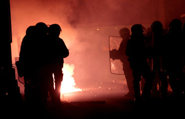 Policemen are silhouetted in front of a fire in Thessaloniki