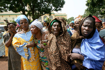 The relatives of Gassim Camara cry as they leave a mosque for the cemetery in Conakry