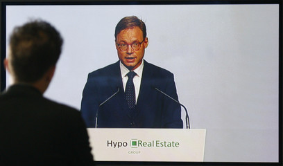 An unidentified man watches the speech of the CEO of German bank Hypo Real Estate Wieandt on a TV screen at the bank's extraordinary shareholders meeting in Munich