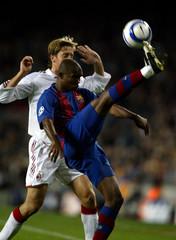 FC Barcelona's Cameroon player Etoo kicks the ball away from AC Milan's Italian player Ambrosini ...